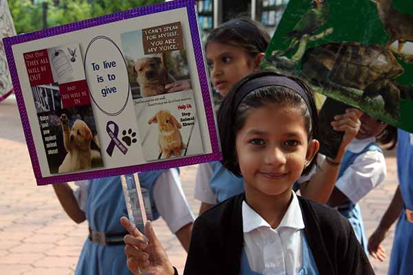 Be kind to save mankind - says the placard of a child as students observe World Animals Day
